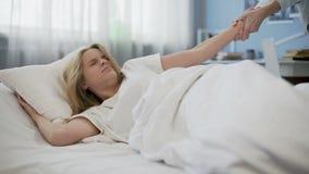 De moeder die tienerdochter in ochtend proberen te wekken, lui meisje gaat op slaap stock video