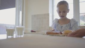 De moeder die vers gebakken cakes op de lijst voor de dochter zetten Het gelukkige meisje die één cake grijpen en stock video