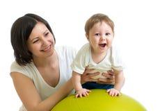 De moeder doet gymnastiek met baby op geschiktheidsbal Stock Afbeelding