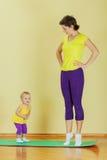 De moeder doet oefeningen met haar dochter Stock Fotografie