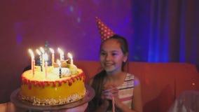 De moeder draagt de heerlijke cake met het branden van multicolored kaarsen