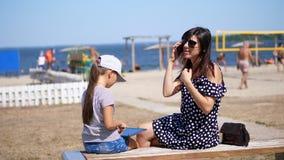 De moeder, een mooie vrouw in zonglazen, met een acht-jaar-oude dochter, zit op het strand op een hete de zomerdag stock video