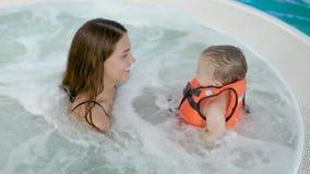 De moeder en de baby zwemmen in de pool stock footage