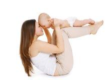 De moeder en de baby doen oefening en hebben pret op een whi Stock Foto