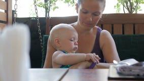 De moeder en de baby kwamen in de koffie en wachten op de orde Jong geitje het spelen met rond iedereen Jong geitje 1 jaar stock videobeelden