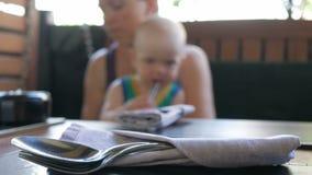 De moeder en de baby kwamen in de koffie en wachten op de orde Jong geitje het spelen met rond iedereen Lepels en vorken in stock videobeelden