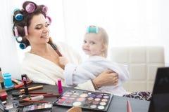De moeder en de dochter doen haar, manicures, make-up, die pret hebben Stock Fotografie