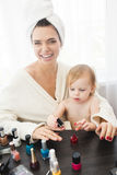 De moeder en de dochter doen haar, manicures, make-up, die pret hebben Royalty-vrije Stock Afbeeldingen