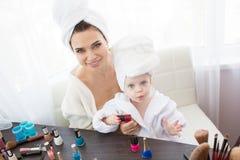 De moeder en de dochter doen haar, manicures, make-up, die pret hebben Royalty-vrije Stock Foto's