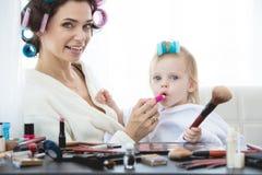 De moeder en de dochter doen haar, manicures, make-up, die pret hebben Stock Afbeeldingen
