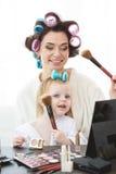 De moeder en de dochter doen haar, manicures, make-up, die pret hebben Stock Afbeelding