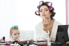 De moeder en de dochter doen haar, manicures, make-up, die pret hebben Stock Foto