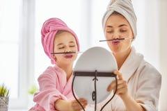 De moeder en de dochter doen omhoog maken Stock Fotografie