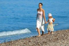 De moeder en de dochter gaan op kust Stock Fotografie