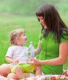 De moeder en de dochter hebben picknick drinkwater Stock Foto