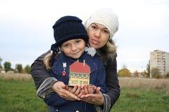 De moeder en de dochter houden een klein plattelandshuisje i royalty-vrije stock afbeeldingen