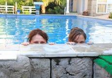 De moeder en de dochter kijken uit de pool stock foto