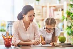 De moeder en de dochter leren te schrijven Stock Afbeelding