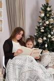 De moeder en de dochter lezen een boek bij open haard op Kerstmisvooravond stock afbeelding