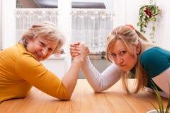 De moeder en de dochter meten de krachten Royalty-vrije Stock Afbeeldingen
