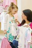 De moeder en de dochter proberen op kleren Stock Foto's