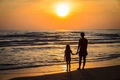 De moeder en de dochter van silhouetten met zonsondergang stock foto