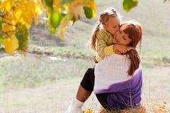 De moeder en de dochter zijn in de herfstpark Stock Afbeeldingen