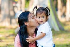 De moeder en de dochter zijn omhelzing en kus De familie is Thailand Stock Fotografie