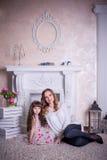 De moeder en de dochter zitten dichtbij de open haard Stock Foto's
