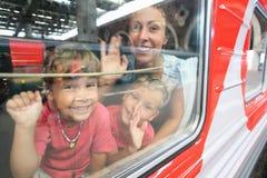De moeder en de kinderen kijken van treinvenster Stock Afbeeldingen