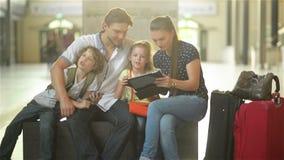 De moeder en de vader met twee kinderen zitten in de wachtkamer van het station of een luchthaven stock footage