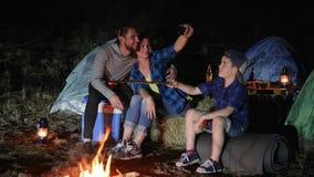De moeder en de vader met zoon die op androïde in aard dichtbij vuur wordt gefotografeerd, gelukkige familie maken foto op mobiel stock footage
