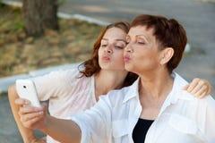 De moeder en de volwassen dochter doen selfie door mobiele telefoon in su Royalty-vrije Stock Afbeeldingen
