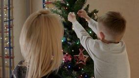 De moeder en de zoon bekijken elkaar en glimlachend en verfraaien Kerstmisboom stock videobeelden