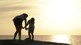De moeder en de zoon blijven op de dagzomende aardlaag overziend het overzees bij zonsondergang en lach stock video
