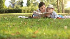 De moeder en de zoon brengen tijd in het park in de zomer door lezend een boek stock video