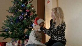 De moeder en de zoon dragen een hoed van de Kerstman onder de Kerstmisboom, stock videobeelden