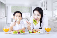 Aziatische familie die gezonde salade thuis eathing Stock Foto's