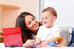 De moeder en de zoon gebruiken laptop Stock Foto