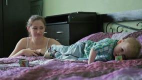De moeder en de zoon hebben pret in bed stock footage