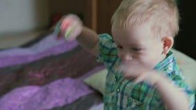 De moeder en de zoon hebben pret in bed stock videobeelden