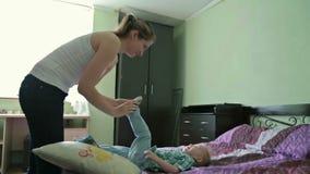 De moeder en de zoon hebben pret in bed stock video