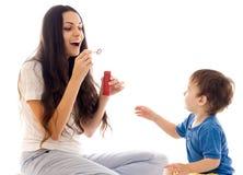 De moeder en de zoon hebben pret samen met zeepbel Stock Foto