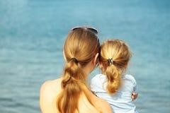 De moeder en de zoon kijken op zee stock fotografie