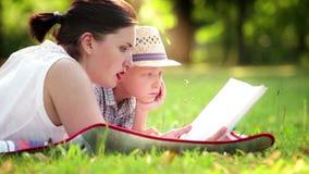 De moeder en de zoon liggen op de dekking in het park en lezen een boek stock videobeelden