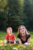 De moeder en de zoon liggen op esdoornbladeren Royalty-vrije Stock Afbeeldingen
