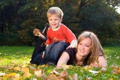 De moeder en de zoon liggen op esdoornbladeren Stock Afbeelding