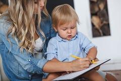 De moeder en de zoon schilderen de muren en de vloer Kinderen` s creativiteit Stock Foto's