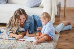 De moeder en de zoon schilderen de muren en de vloer Kinderen` s creativiteit Royalty-vrije Stock Fotografie