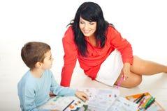 De moeder en de zoon zitten bij vloer en het spreken Stock Foto